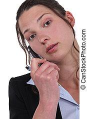 Secretary holding mobile telephone and pen