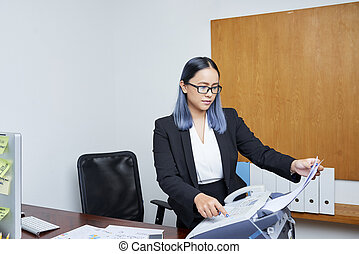 Young Asian businesswoman with blue hair printing out document via fax machine