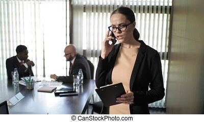 Secretary talking on the phone and screaming at businessmen during the meeting
