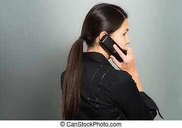 Secretive businesswoman talking on her mobile phone standing facing away from view while glancing back surreptitiously to ensure her privacy, on a gray background with copyspace