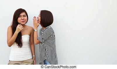Secrets - two young asian good friends sharing secrets.