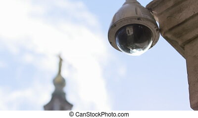 Close up of a security camera on a building across the street from the Lady Justice statue atop Old Bailey