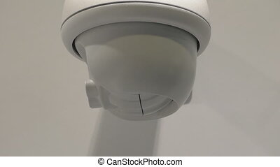 Security camera working - CCTV camera fixed on white wall...