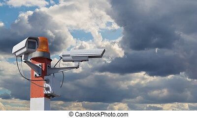 Time lapse video with two CCTV security cameras on red striped pillar with orange flashing light against a cloudy sky with moving and swirling clouds