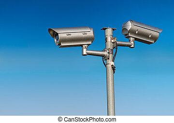 Security CCTV video camera against blue sky.