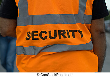 Back of a security guard in orange uniform jacket