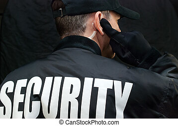 Security Guard Listens To Earpiece, Back of Jacket Showing...