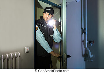 Security Guard Searching With Flashlight In Room