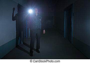 Security Guard Standing In Corridor Of Building