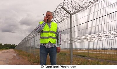 Security guard using walkie talkie near wire fence