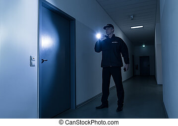 Security Guard With Flashlight Standing In Front Of Door
