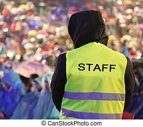 security guard with safety vest with STAFF text controls people during an important event