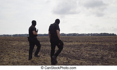 security guards in full equipment, gun, body armor, masks inspect the territory