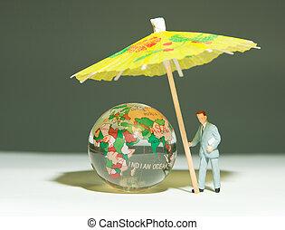 Security man holding umbrella under globe