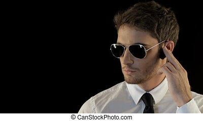 Security man looking to the sides isolated against black background. Brunette man making movements like bodyguard. Cool man in aviator sunglasses taking a look around