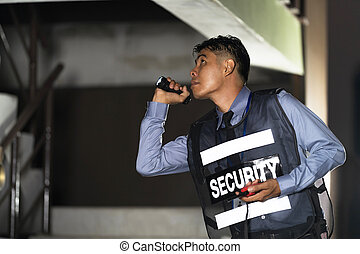 Security man standing outdoors with flashlight in building