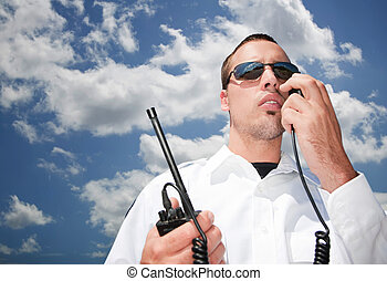 Security guard using hand-held radio for communication