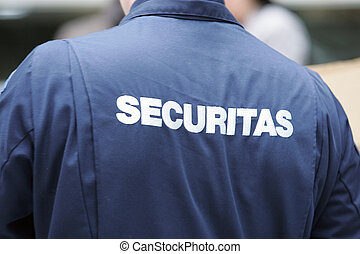 security wearing an overall with the word securitas on it