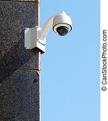 Security / surveillance camera against a clear blue sky
