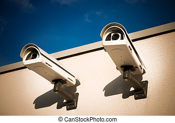 Security video cameras on a wall.