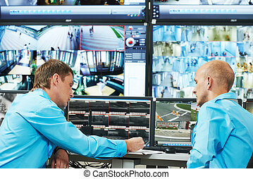 Security video surveillance - two security guards watching...