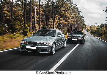 Sedan cars driving on the forest road and passing each other