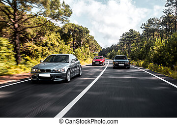 Sedan cars driving on the forest road