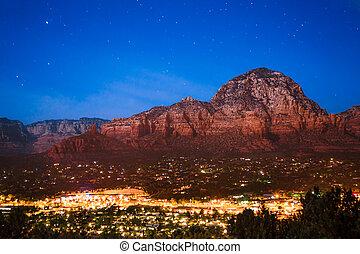 Beautiful Sedona Arizona at night with red rock mountains and city lights