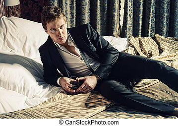 seduction - Attractive handsome man in elegant suit lying on...