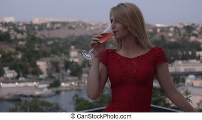 Seductive blonde in the red evening dress drinking champagne on the outdoors terrace at the restaurant