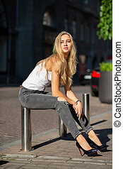 Seductive blonde model with long hair wearing jeans and t shirt posing at the city in sun rays