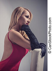 Seductive blonde woman in red dress sitting on chair