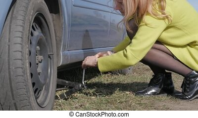 seductive blonde woman trying change wheel on a car on rural road. 4K