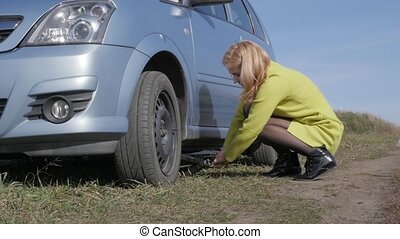 seductive blonde woman trying change wheel on a car on rural road. slow motion