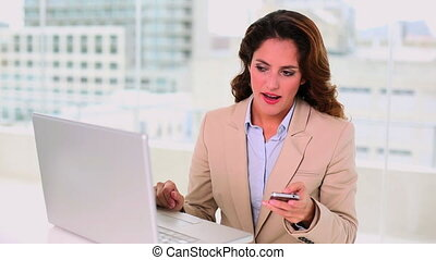 Seductive brunette businesswoman typing on laptop while...
