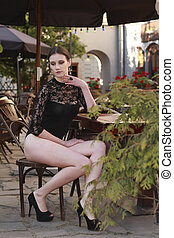 Seductive brunette model in lace lingerie posing at the street cafe