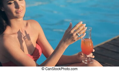 Seductive brunette with long hair dressed in bikini drinking cocktail while sitting near the pool