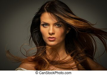 Seductive fatal brunette woman with long hair