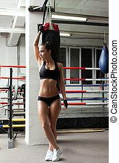 Seductive female boxer posing in gym