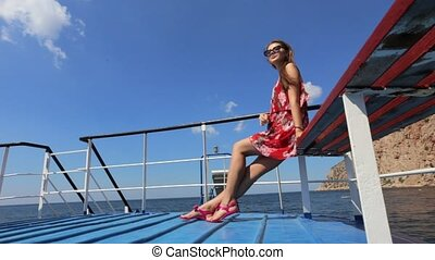Seductive girl in the red sundress and sunglasses sitting on the ship