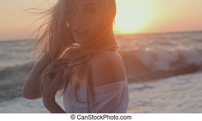 Seductive girl withe long hair posing at sunset on the beach