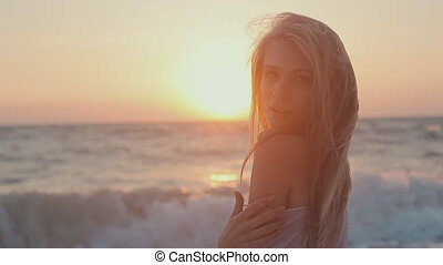 Seductive girl with blong long hair dressed in a transparent tunic posing at sunset on the beach