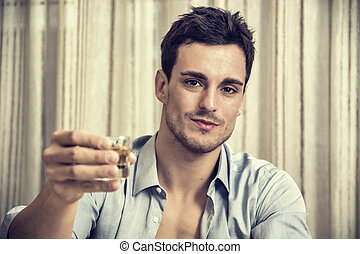 Seductive handsome young man sitting drinking