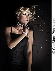 Attractive seductive woman tearing her pearl beads isolated on black background, broken luxury jewellery, desire concept