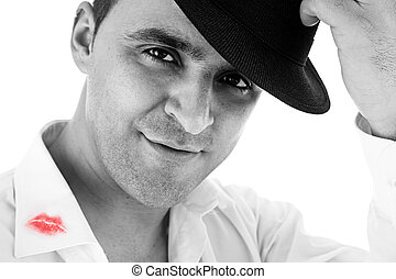 seductive man greeting with his hat and shirt with lipstick mark, on white background