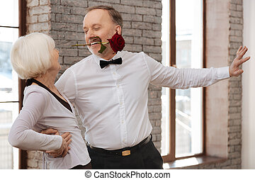 Seductive man tangoing with senior woman in the dance studio