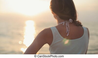 Seductive model with beautiful smile standing back to the camera near the sea at sunset