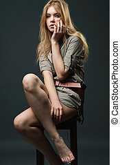 Seductive portrait of young woman sitting on chair