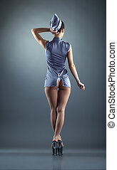 Seductive stewardess posing back to camera, on gray...