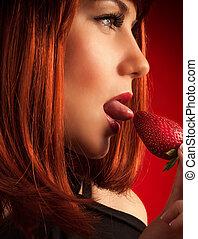 Seductive woman eating strawberry